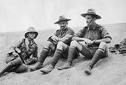 An informal black and white group portrait of three men in military uniform. They are sitting on the ground in what appears to be a desert.