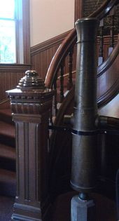 An old brass cannon mounted vertically next to a curved stairway in a lobby with wooden paneling.