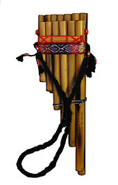 A siku pan flute with two rows of bamboo chutes cut to graduated lengths. The chutes are aligned so that their tops are level (for embouchure). The chutes are bound in a combination of braided and woven yarn, including a woven strap with a traditional pattern. An additional strap is attached to the left and right sides of the flute, so that it may be worn around th neck.