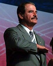 El ex-presidente Vicente Fox haciendo el saludo civil a la bandera nacional.
