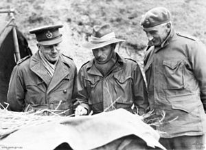 Three men study a map. They are wearing military uniforms, with a peaked cap, a slouch hat and a beret, but are dressed warmly  against the cold with scarves and gloves.