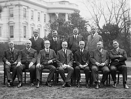 Coolidge's cabinet in 1924, outside the White House. Front row, left to right: Harry Stewart New, John W. Weeks, Charles Evans Hughes, Coolidge, Andrew Mellon, Harlan F. Stone, Curtis D. Wilbur. Back row, left to right: James J. Davis, Henry C. Wallace, Herbert Hoover, Hubert Work. Coolidge Cabinet.jpg