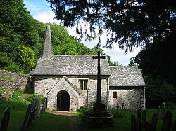 A small stone church surrounded by trees