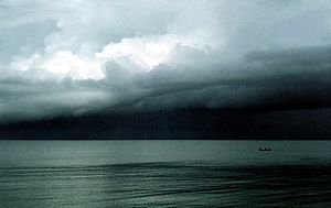 Three fishermen under dark storm clouds at Bo-...