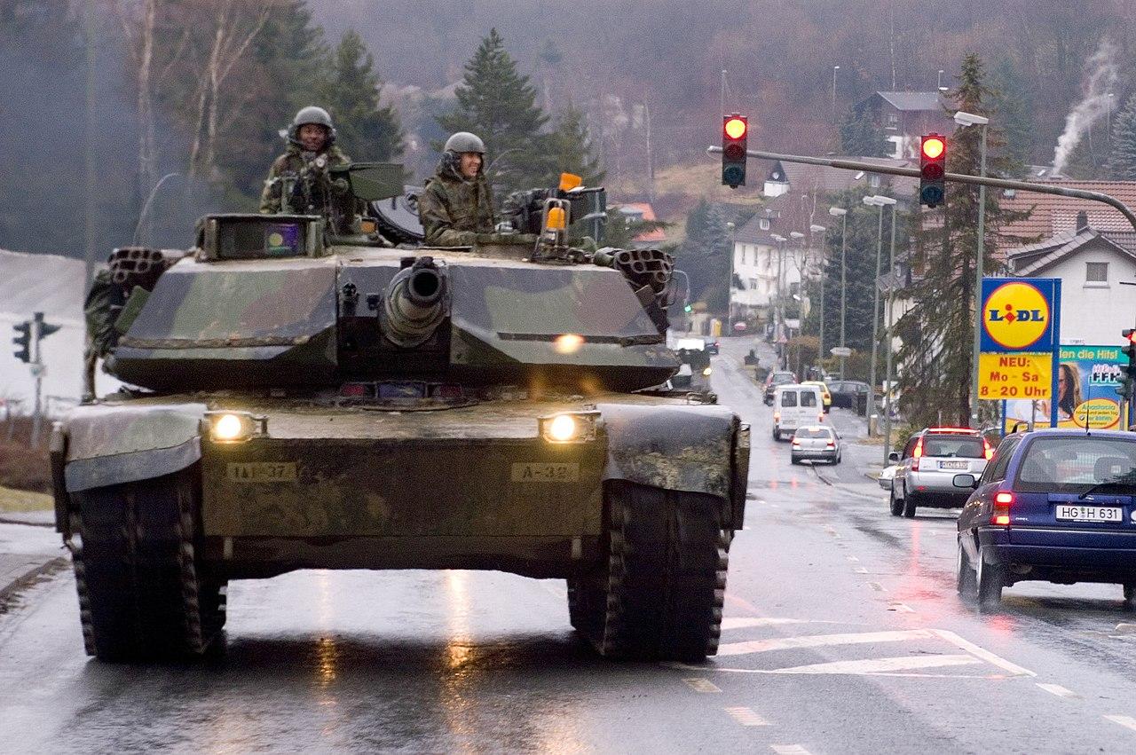 US-Panzer fährt durch Ortschaft.