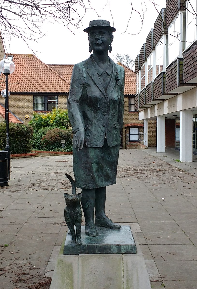Statue of a woman wearing a hat and skirt suit, with a cat brushing by her legs