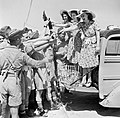 ENSA (Entertainments National Service Association) 'glamour girls' distribute cigarettes and beer to the troops in North Africa, 26 July 1942. E14919.jpg
