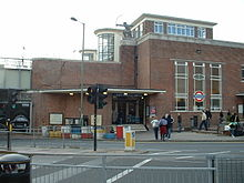 A plain red brick station entrance building. A statue of a knelling archer sits on a stone capped wall