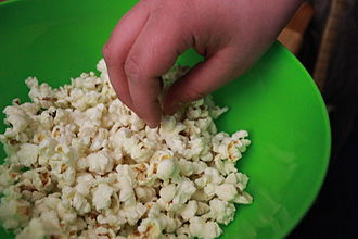 Popcorn - A person eating popcorn out of a bowl