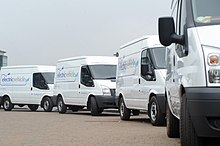 """Four white cargo vans, based of the third-generation facelifted Ford Transit but with electric powertrains, made for left-hand traffic, each with the words """"electric vehicle"""" visible in big letters on its right side and in smaller letters on the front-facing part of its raised roof, and with the 2011 logo of the University of Warwick visible on the right (driver's) door"""