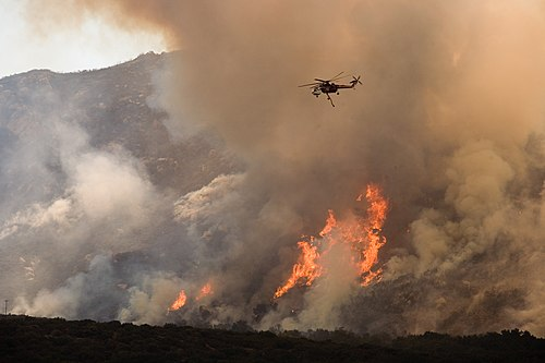 A helicopter drops water on a wildfire in California. Drought and higher temperatures linked to climate change are driving a trend towards larger fires. FEMA - 33364 - A helicopter drops water on the wildfire in California.jpg