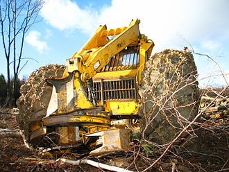 Feller buncher - Older style felling head that uses a bar and chain to cut trees instead of the more modern saw disk.