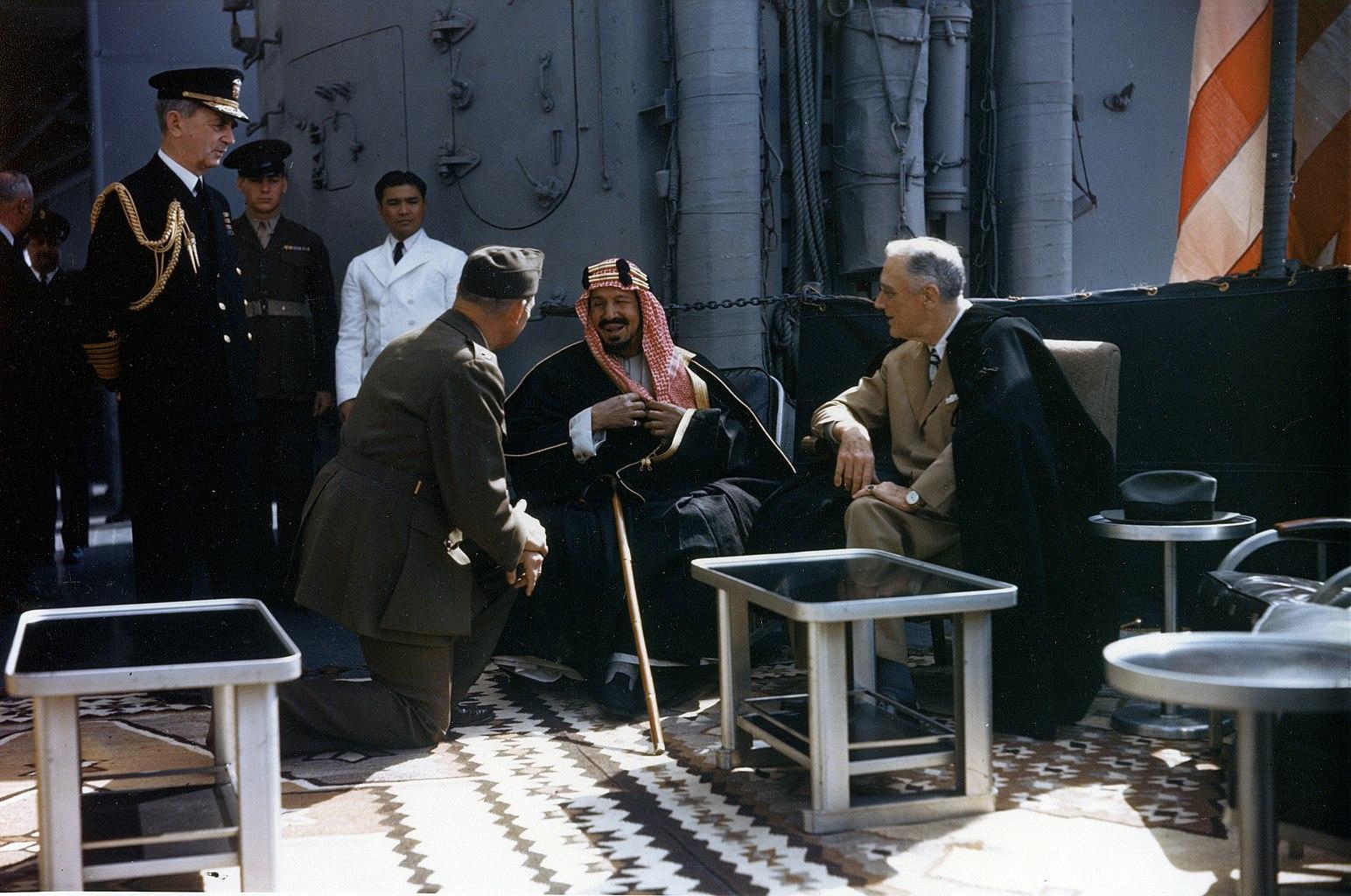 Le président Franklin Roosevelt en compagnie du roi Abdelaziz Al Saoud, du colonel William A. Eddy(en) (qui sert d'interprète, un genou au sol) et de l'amiral William Leahy (debout, à gauche) sur l'USS Quincy.