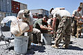From left, U.S. Navy Lt. Cmdr. Tom Karnowski and Marine Corps Sgt. Daniel Holden, both with Combined Joint Interagency Task Force 435, help make fuel donuts for an Operation Outreach Afghanistan program at Camp 130728-F-JL359-003.jpg
