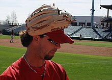 A brown-haired young man with a goatee wearing a tan baseball glove on his hand atop a red baseball cap