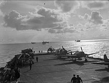 Black and white photograph of single propeller fighter aircraft on the deck of an aircraft carrier at sea. Several other ships are visible in the background.