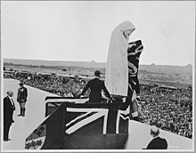 A figure standing on flag-covered stage located in front of the statue of Canada Bereft