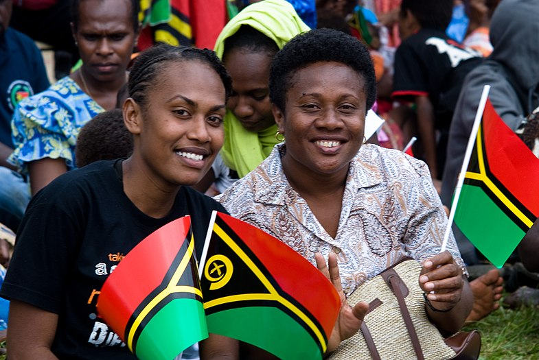 Photograph of two women smiling and holding small plastic Vanuatu flags