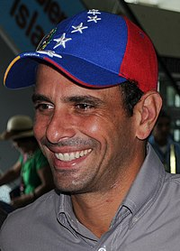 A man smiling while wearing a hat with the colours of the Venezuelan flag: red, blue and yellow.