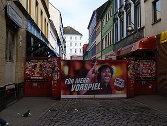 "Reeperbahn - Entrance to Herbertstraße; red sign to the right of the gate reads ""No entrance for juveniles under 18 years of age and women"". The large cigarette ad reads literally, ""...For more foreplay."""