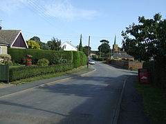 Semi-suburban village road, with the copper-clad church spire in the distance.