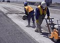 Highway construction workers using concrete saws (9245787233).jpg