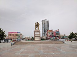 The Monument of Kurban Tulum's shaking hands with Mao Zedong is in the center of Tuanjie Square, Hotan, China