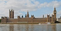 View of the long Parliament building, as seen from the southern bank of the Thames. On the left of the building is the Victoria Tower, flying the Union Flag; on the right is the Elizabeth Tower (often called Big Ben).