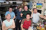 ISS-48 Crew members in the Zvezda service module sharing a light moment and a meal.jpg