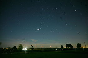 Night sky with a very bright satellite flare