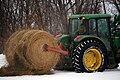 John Deere tractor with round hay bale.jpg