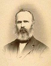 Portrait of a middle-aged man with full beard and thinning hair is wearing a formal jacket.