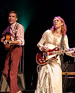 A skinny man in a white shirt and burnt red pants on stage stares into the camera while Welch next to him in a white dress focuses on playing her guitar. The man looks to be in his 20s.