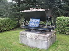 A monument commemorating the beginning of the oil shale industry, consisting of a grey concrete block about 1.5 metres wide and three-quarters of a metre deep. The block is topped by a black metal hopper filled with rocks. A blue plaque with white Estonian-language lettering just above the block explains its significance.