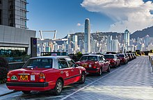 Taxis lined up along a drive outside a building. In the background is a city skyline with tall skyscrapers and a ridgeline under a blue sky with some clouds.