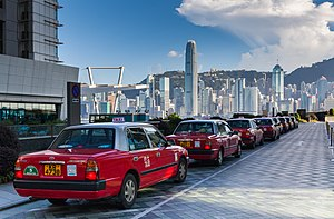 Red cars with signs indicating that they are taxis lined up along a drive outside a building. In the background is a city skyline with tall skyscrapers and a forested ridgeline under a blue sky with some clouds.