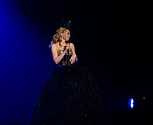 Kylie wears a feather dress with a gold corset on, holding a microphone looking towards her audience. She is also wearing a hat standing in front of a dark blue and black background (2011).