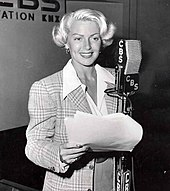Woman in front of a microphone holding sheath of paper