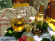 "Colour photo illustrating well the song ""Ah, the little white wine ..."". A carafe of white wine with a full glass and a corked bottle is placed on vine leaves, themselves on a white tablecloth with red tiles. The bottle covered with mist gives a feeling of freshness and the play of light and shadow suggests that the scene is set under a Pergola."