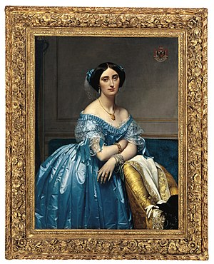 Pauline de Broglie is shown seated on a upholstered easy chair. She wears a pale blue satin ball gown and lavish jewelry