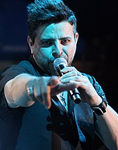A man holding a microphone to his mouth with his right hand and pointing at the frotn with his left hand.