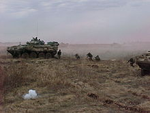 Two tanks and five soldiers on uneven ground. The soldiers are crouching between the two tanks