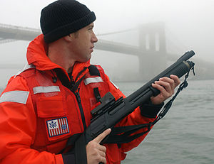 Remington Model 870 - A U.S. Coast Guard petty officer from Maritime Safety and Security Team 91106 armed with an Mķ870P fitted with a Trijicon reflex sight and a Speedfeed stock.