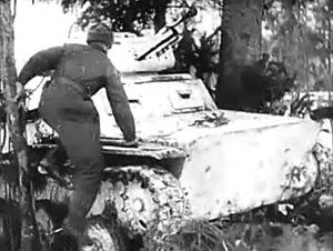 Moscow Strikes Back - A crewman jumps aboard his snow camouflaged tank