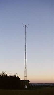 Tall antenna tower on a background of twilight clear sky; small shack is at bottom of tower
