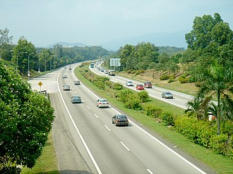 Malaysian Expressway System - South section of North–South Expressway near Pedas-Linggi, Negeri Sembilan, facing towards Kuala Lumpur (before being upgraded into six-lane carriageway from 1 July 2005 until 1 July 2007) with Titiwangsa Mountains in the top peak