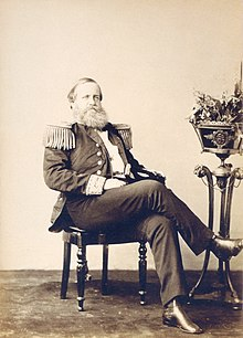 Photograph of a bearded man seated casually with crossed legs and wearing a military tunic with fringed epaulettes