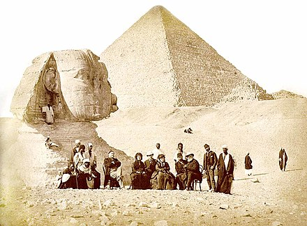 French archaeologist Auguste Mariette (seated, far left) and Pedro II of Brazil (seated, far right) with others during the Emperor's visit to the Giza pyramid complex at the end of 1871 Pedro II of Brazil in Egypt 1871.jpg