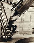 A man sitting on a chair mounted to a moving platform, staring through a large telescope.