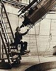 一个人坐在安装一个移动的平台的椅子,通过大型望远镜观测。